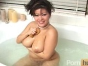 Asian MILF toys herself in the bath