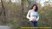 Brunette pisses on a footpath