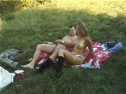 man EATS pretty blonde on a blanket at the picnic