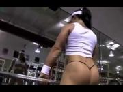 Chica musculosa ejercitandose en micro tanga