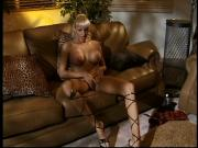 Big chested blonde slut grips a hard cock while sitting on a couch