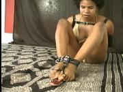 Yana bound in armbinder dials phone with toes