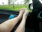 mature bare feet and legs in the car