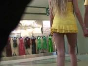 Gorgeous blonde with short yellow dress walking in shopping.