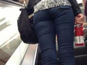 Denim jeans ass going up the escalator