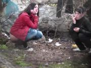 Two girls pee in the woods