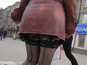 Girl in sexy stockings walking in a street