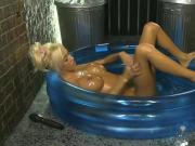 Kerrie Lee in a paddling pool covered in oil