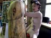 Emo girl fucks a giant wooden dildo.