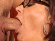 Mature woman in eyeglasses riding a cock