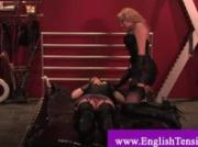 Dominatrix in high heels stands on slaves chest