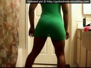 Ebony girl booty dancing in a green dress