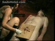 Beautiful mistress puts wooden clamps on balls of slave and