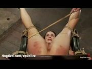 Hogtied brunette gets legs and ass whipped