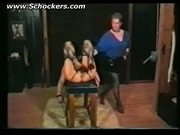 Dominatrix hits hot slave who is tied to a table in a dungeo