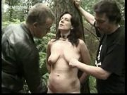 Horny slave is tied to a tree and fucked with a dildo and hi