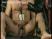 Slave with his balls tied together with a rope is spanked by