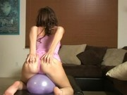 Lovely girl sitting on a purple balloon and popping it