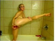 Blonde plays with a red dildo in the shower