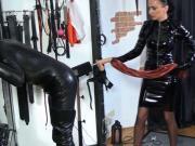 A vinyl domina whips her slave