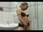 Busty brunette fingering on the toilet