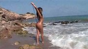 Hot black chick gettin' wet on beach