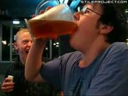 nerd chugs a massive glass of beer in a few seconds