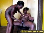 Two African lesbians play with each other using sex toys