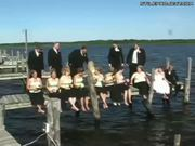 Wedding party sitting on dock for picture falls into the lake