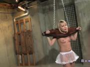 Blonde shackled in wooden restraints