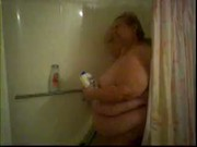 Fat aged woman washes amenities in steamy shower