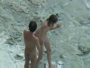 A pair is getting nauhty on the beach while someone is shootig them secretly