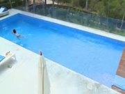Naked brunette swiming in the pool.