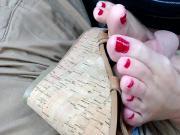 Rubbing red toenails on thick cork platform sandals