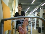 Barefoot brunette in a public library