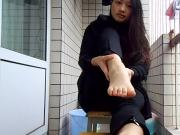 Pretty Asian on patio spreading toes