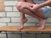 Dirty feet outside on wooden bench