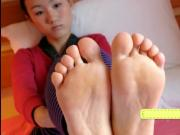 Young chinese girl playing with her delicious small feet