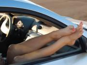 Dangling beautiful feet out of fast car