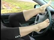 Feet sensually rubbing car's interior