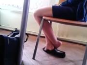 Black flats dangling under a desk
