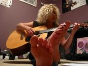 Toes up close while she sings and plays guitar
