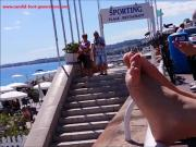 This Woman With Red Toe Nails Relaxes Her Luscious Feet On The Railing At The Beach