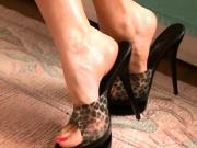 Leopard peeptoe mules on tan carpet