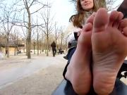 Hot Older Woman Relaxes On a Bench In The Park And Shows The Camera Her Bare Feet