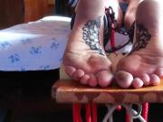 Tattoed soles bound in ankle cuffs