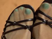 Turquoise toenails show through her tan pantyhose