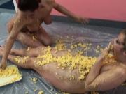 Blonde and brunette slather macaroni & cheese all over themselves